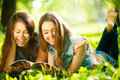 Teenage girls reading a magazine outdoors Royalty Free Stock Photo