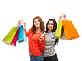 Teenage girls with shopping bags and credit card sale gifts concept two smiling Royalty Free Stock Image