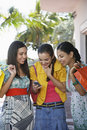 Teenage Girls With Shopping Bags Text Messaging Royalty Free Stock Photo