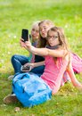 Teenage girls sitting on grass and taking selfie Royalty Free Stock Photo