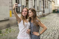 Teenage girls take pictures of themselves on the smartphone on the street. Royalty Free Stock Photo