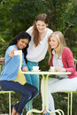 Teenage girls taking photo on mobile phone at outdoor cafe café and smiling Stock Image
