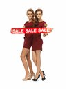 Teenage girsl in red dresses with sale sign Royalty Free Stock Photo