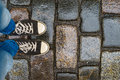 Teenage legs in sneakers on wet pavement Royalty Free Stock Photo
