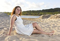 Teenage model on the beach with a white dress sitting she is happy and smiling at camera Royalty Free Stock Photo