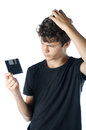 Teenage puzzled with floppy disk in his hand isolated on white Stock Images