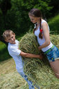 Teenage sister and little brother holding velour grass or hay on summer outdoors background Stock Image