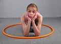 Teenage sportive girl is doing exercises with hula hoop to develop muscle on grey background having fun playing game sport heal Royalty Free Stock Photos