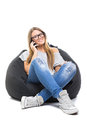 Teenage student girl with eyeglasses speaking on the phone cute blonde caucasian wearing casual clothes sitting a beanbag Stock Photo
