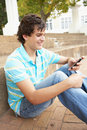 Teenage Student Sitting Outside Using Mobile Phone Royalty Free Stock Images
