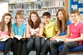 Teenage Students In Library Reading Books Stock Photo