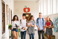 Teenage students walking in high school hall, talking. Royalty Free Stock Photo