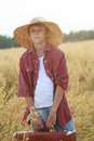 Teenage traveler in farm ripe oat field with old-fashioned brown suitcase looking at camera