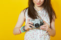 Teenage woman holding a retro film camera close up of hipster setting up her over yellow background Stock Image