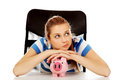 Teenage woman with piggybank on the table Royalty Free Stock Photo