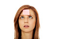Teenage woman with sticky notes on forehead