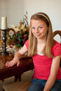 Teenaged girl sitting at wood dining table Stock Image