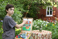 Teenager artist  boy in garden painting picture of jasmin flowers and cottage house Royalty Free Stock Photo