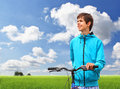 Teenager with bicycle in field happy smiling a bike standing a Stock Photo