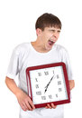 Teenager with big clock tired yawning and holding isolated on the white background Royalty Free Stock Images