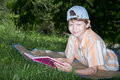 Teenager with book the in cap lays on grass the in hands Royalty Free Stock Images