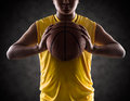Teenager boy holding a basket ball isolated on black Stock Image