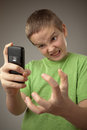 Teenager boy and mobile phone portrait on a gray background Stock Images