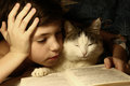 Teenager boy reading book in bed with sleeping cat Royalty Free Stock Photo