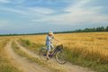 Teenager boy rides a bicycle on country road Royalty Free Stock Photo