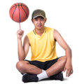 Teenager boy sitting with basketball isolated over white clipping path Stock Photos