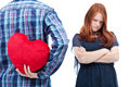 Teenager boy trying to ask forgiveness with red heart pillow sad girlfriend isolated Royalty Free Stock Images