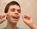 Teenager brushing his teeth with dental floss Stock Photos