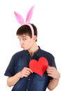 Teenager with bunny ears and heart funny red shape on the white background Stock Photo