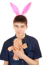 Teenager with bunny ears infantile and teddy bear isolated on the white background Stock Photography