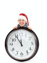 Teenager in cap of Santa Claus and large clock Royalty Free Stock Photos