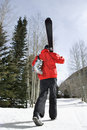 Teenager carrying ski gear. Royalty Free Stock Photos