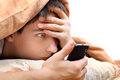 Teenager with cellphone frightened under blanket at the home Royalty Free Stock Images