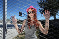Teenager clings to the metal mesh of the playground with fedora hat and sunglasses Royalty Free Stock Photography
