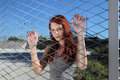 Teenager clings to the metal mesh of the playground with red hair Stock Photography