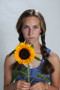Teenager cute serious girl with pigtails and sunflower Royalty Free Stock Image
