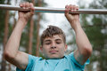 Teenager doing exercise on a horizontal bar the Royalty Free Stock Photography