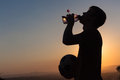 Teenager drinks football silouette s has a water drink after playing game silhouetted at sunset Stock Photo