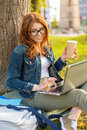 Teenager in eyeglasses with laptop and coffee education technology internet concept smiling redhead computer take away or tea Royalty Free Stock Image