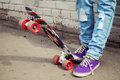 Teenager feet in jeans and snickers with skateboard near gray urban brick wall photo retro tonal correction instagram old Stock Photos