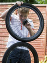 Teenager fixing bicycle wheel Royalty Free Stock Images