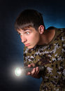 Teenager with flashlight surprised in camouflage t shirt on the dark background Royalty Free Stock Photography