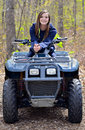 Teenager on a four wheeler beautiful with braces trail in the woods Royalty Free Stock Photos