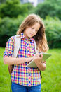 Teenager girl with backpack and digital tablet outdoor portrait of a beautiful in casual clothes holding in her hand typing Royalty Free Stock Photos