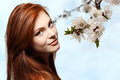 Teenager girl beautiful red hair cheerful enjoying over spring b flower background Royalty Free Stock Photo