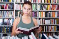 Teenager girl brunete looks for the right book in library Royalty Free Stock Photo